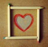 Herz gezeichnet auf Papier in einem Rahmen von farbigen hölzernen Bleistiften Stockbilder