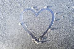 Herz gezeichnet in den Frost auf der Haube des Autos Stockbild