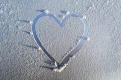 Herz gezeichnet in den Frost auf der Haube des Autos Lizenzfreie Stockfotografie