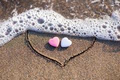 Herz gezeichnet in den Sand mit zwei Herzen Stockfotografie