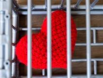 Herz im Käfig, der auf einen Holztisch gesetzt wird, zeigt es die Schließung der Freiheit und der Liebe Liebe ist enttäuscht und  Stockfoto