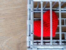 Herz im Käfig, der auf einen Holztisch gesetzt wird, zeigt es die Schließung der Freiheit und der Liebe Liebe ist enttäuscht und  Lizenzfreies Stockbild