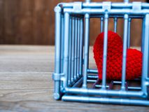 Herz im Käfig, der auf einen Holztisch gesetzt wird, zeigt es die Schließung der Freiheit und der Liebe Liebe ist enttäuscht und  Stockbilder
