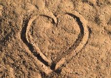 Herz im Sand auf dem Strand bei Sommersonnenuntergang Lizenzfreie Stockfotografie