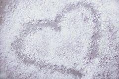 Herz im Schnee auf grauem Hintergrund Stockfotos
