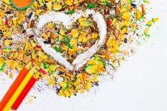 Herz, mehrfarbige Bleistifte und varicolored hölzerne Schnitzel Lizenzfreie Stockfotografie
