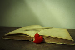 Herz mit altes Buch Stillleben, Weinleseart Lizenzfreie Stockfotos