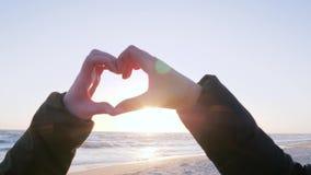 Herz mit den Fingern auf Hintergrund des Wassers und des rosa Himmels bei Sonnenuntergang stock footage
