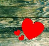 Herz mit drei Rottönen des Papiers auf hölzernem Hintergrund des alten Schmutzes Stockfotografie