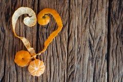 Herz mit orange Schale auf hölzernem Hintergrund Stockfoto