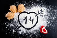 14 Herz mit Pfeil auf dem Mehl auf der schwarzen Tabelle Plätzchen Lizenzfreie Stockbilder