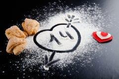 14 Herz mit Pfeil auf dem Mehl auf der schwarzen Tabelle Plätzchen Stockbild