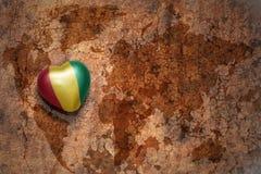 Herz mit Staatsflagge der Guine auf einem Weinleseweltkartesprungs-Papierhintergrund stockfotos