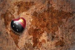 Herz mit Staatsflagge von Papua-Neu-Guinea auf einem Weinleseweltkartesprungs-Papierhintergrund lizenzfreie stockfotografie