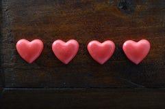 Herz mit vier Rottönen auf hölzernem Hintergrund Stockbilder