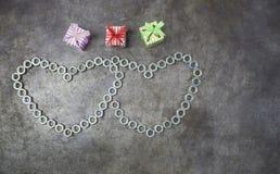 Herz mit zwei Nüssen und Geschenk drei auf dem Metallhintergrund für Valenti Lizenzfreies Stockfoto
