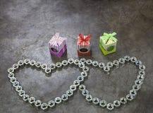 Herz mit zwei Nüssen und Geschenk drei auf dem Metallhintergrund für Valenti Stockfotos