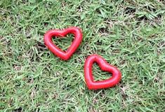 Herz mit zwei Rottönen auf dem Gras Stockfoto