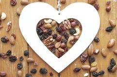 Herz, Nüsse und Rosinen auf hölzernem Hintergrund Stockfoto