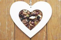 Herz, Rosinen und Nüsse auf hölzernem Hintergrund Lizenzfreie Stockbilder