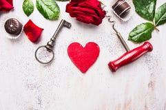 Herz, Rotrose, Schokolade, Schlüssel und Korkenzieher auf weißem hölzernem, Liebeshintergrund Stockfotografie