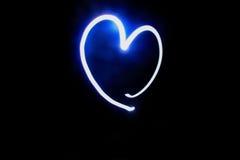 Herz schaffen durch Fackel auf schwarzem Hintergrund stockfoto