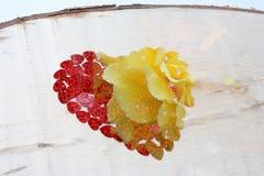 Herz und Blume auf hölzernem Hintergrund Rotes Herz und gelbe Blume Stockbild