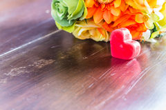 Herz und Blumen auf hölzernem Lizenzfreie Stockbilder