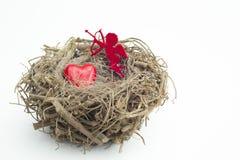 Herz und die Amorzahl, die in einen hölzernen Vogel gesetzt wird, nisten Stockfotografie
