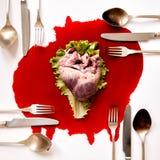 Herz und Tischbesteck in einem Blutpool Stockfoto