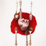 Herz und Tischbesteck in einem Blutpool Stockbilder