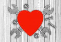 Herz und Werkzeuge über hölzernem Hintergrund Konzept: Erneuerung lizenzfreie stockfotos