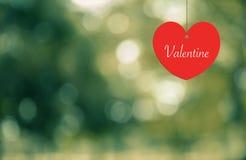 Herz-Valentinsgruß, der an einem Seil auf abtract Hintergrund hängt Stockfoto