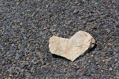 Herz vom hellen Stein auf dunklen Steinen Stockfotografie