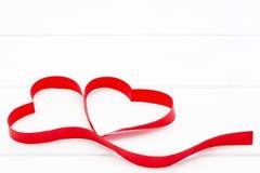 Herz vom roten Band auf weißem hölzernem Hintergrund Stockbild