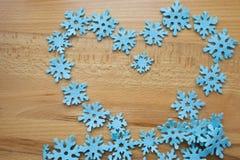 Herz von blauen Schneeflocken auf einem hölzernen Hintergrund Lizenzfreies Stockfoto