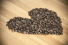 Herz von coffe Bohnen auf dem Tisch Stockfotos