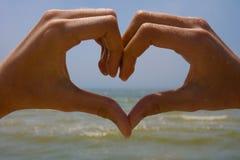 Herz von den Händen auf dem Hintergrund des Meeres stockfoto