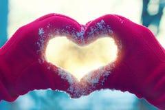 Herz von den Händen auf Winterhintergrund stockbild