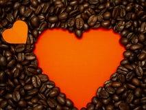 Herz von den Kaffeebohnen auf Rot lizenzfreie stockbilder