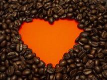 Herz von den Kaffeebohnen auf Rot stockfoto