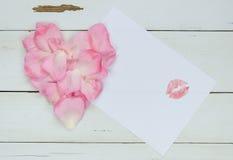 Herz von den rosafarbenen Blumenblättern, freier Raum für Ihren Text mit Lippenstiftkuß Lizenzfreies Stockbild
