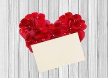 Herz von den roten rosafarbenen Blumenblättern und vom Papier auf Holztisch Stockfoto