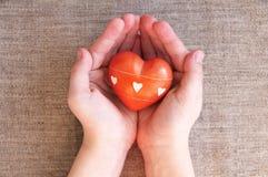 Herz von einem Stein in den Kinderhänden Lizenzfreies Stockfoto