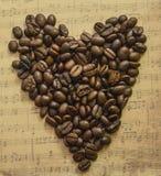 Herz von Kaffeebohnen auf dem Hintergrundmusikblatt Stockbilder