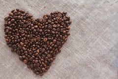 Herz von Kaffeebohnen auf Leinendraufsicht Stockbild