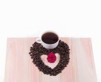 Herz von Kaffeebohnen und von weißem Schalen- und Schwarzemkaffee mit Blume Lizenzfreies Stockfoto