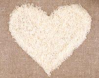 Herz von Reiskörnern auf Leinenhintergrund Lizenzfreies Stockfoto