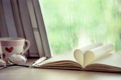 Herzbuchseite auf regnerischer Tagesfensterhintergrund Lizenzfreies Stockbild