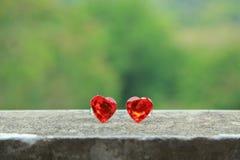 2 Herzen auf dem Zement breiten den grünen Hintergrund aus Stockfoto